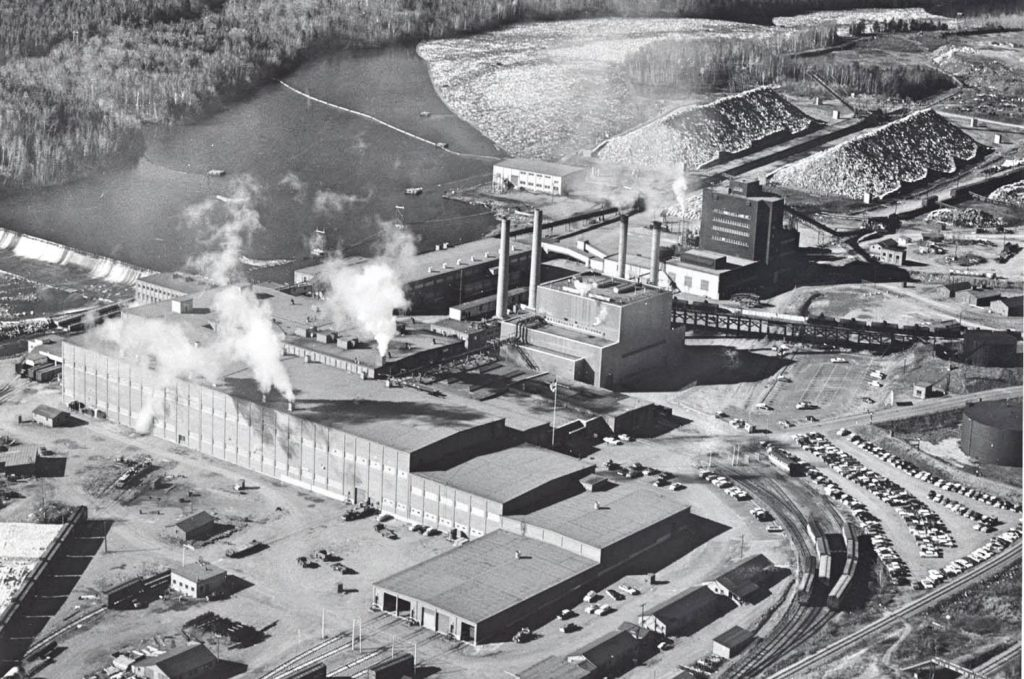 Aerial view of East Mill with logs in the river